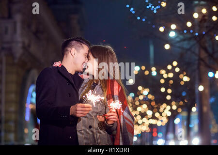 A young couple with sparklers in the hands at Christmas. - Stock Photo