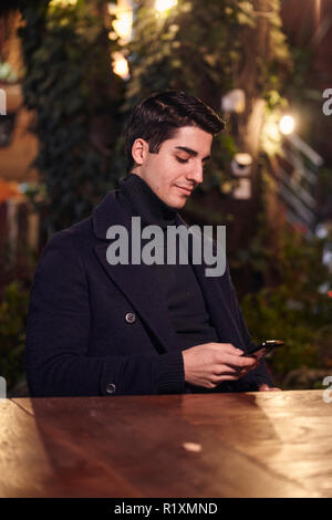 one young handsome man, sitting in cafe garden at night outdoors, texting using smartphone.