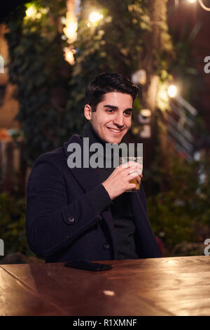 one young handsome man, sitting in cafe garden at night outdoors, holding glass full of juice.