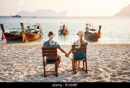 Young couple sitting on the chairs on the tropical beach of Phi Phi island in Southern Thailand. Travel magazine concept. - Stock Photo