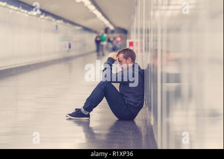 Miserable jobless young man crying Drug addict Homeless in depression stress sitting on ground street subway tunnel looking desperate leaning on wall