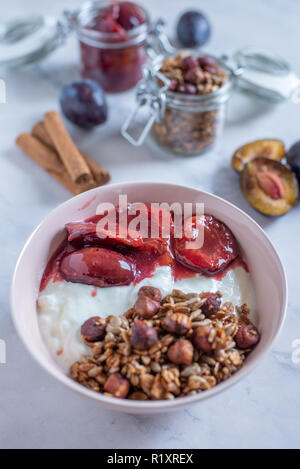 yogurt with plums and home made granola - Stock Photo
