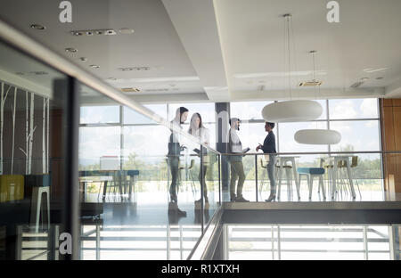 Group of business people walking and taking at stairs in an office - Stock Photo
