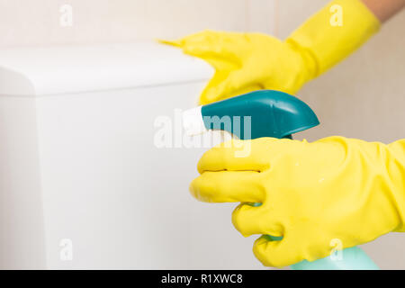 Selective focus picture of disinfectant spray held by person wearing sanitary gloves cleaning wc - Stock Photo
