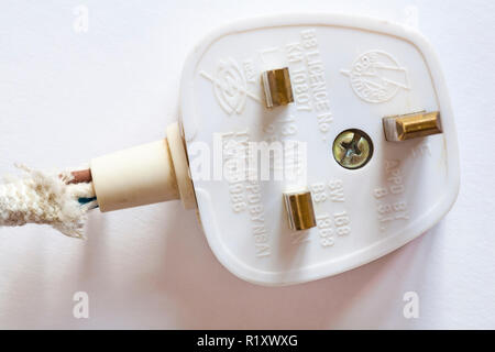 Old dusty 3 pin electrical UK plug with frayed wiring set on white background - Stock Photo