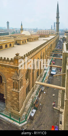 The side wall of Al-Hussain mosque, notable landmark of Islamic Cairo district, surrounded by dirty streets of Souk Khan El-Khalili, Egypt. - Stock Photo