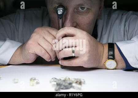 Moscow, Russia. 12th Nov, 2018. A man checks a piece of diamond in an Alrosa facility in Mirnyi, Republic of Sakha (Yakutia), Russia, on Nov. 12, 2018. Alrosa, the world's leading diamond miner, has operations in Republic of Sakha (Yakutia) and Arkhangelsk region, running 11 kimberlite pipes and 16 alluvial deposits in the harsh climate of the Russian Far North. Credit: Evgeny Sinitsyn/Xinhua/Alamy Live News - Stock Photo