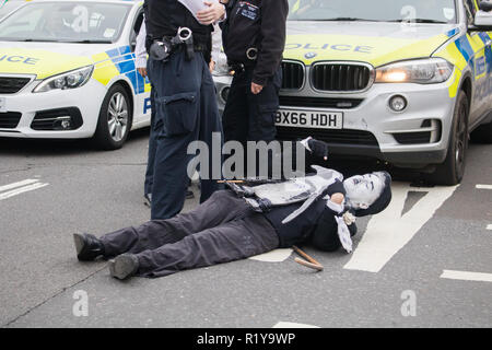 London, UK. 15th Nov, 2018. A climate-change activist, dressed as the comedian Charlie Chaplin is arrested by police officers after blocking traffic outside the Palace of Westminster  as a protest for Government to take climate change more seriously Credit: amer ghazzal/Alamy Live News - Stock Photo