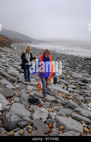 Lyme Regis UK 15th November 2018 - Walkers pick up plastic and litter on the beach between Lyme Regis and Charmouth on a misty dull afternoon along the Jurassic coastline in Dorset Credit: Simon Dack/Alamy Live News - Stock Photo