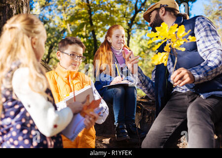 Delighted curious children listening to their teacher - Stock Photo