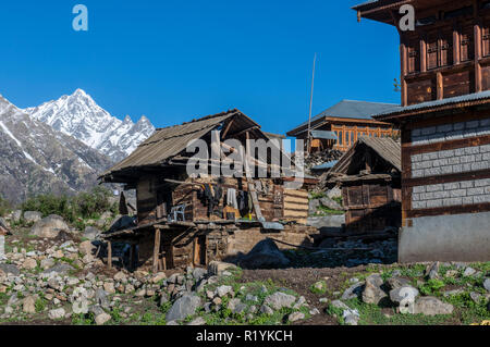 Wooden houses of Chitkul, the last village of Sangla Valley, located at 3.400 m and surounded by snow covered mountains - Stock Photo
