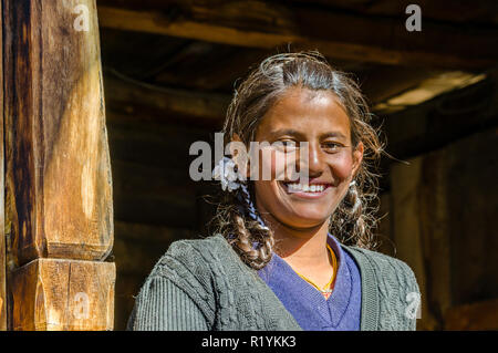 A local girl smiling in front of a wooden house in Chitkul, the last village of Sangla Valley, located at 3.400 m and surounded by snow covered mounta - Stock Photo