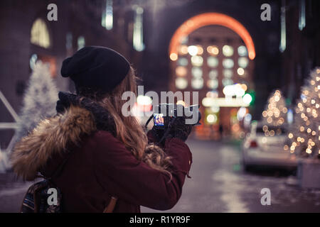 Traveler girl walking through the night city street taking photos of buildings and Christmas trees - Stock Photo