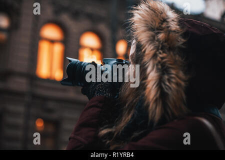 Hipster girl traveler with professional camera walking through the evening city street taking photos - Stock Photo