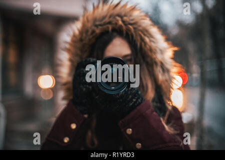 Young female traveler with professional camera walking through the evening city street taking photos - Stock Photo