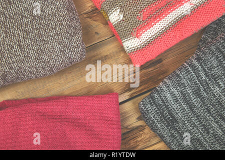 a144717281 Autumn knitted sweaters and leaves  Stack of cozy knitted sweaters. A pile  of warm sweaters on a wooden table on