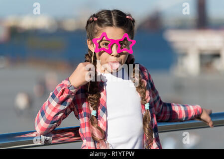Getting ready for party. Small naughty girl having fun. Fashionable glasses for celebration. Stylish look. Disobedient small girl showing her tounge. Positive moments. Concept of childish carelessness. - Stock Photo