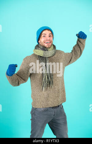 Man knitted hat gloves and scarf winter fashion. Man wear knitted accessory turquoise background. Winter accessories concept. Winter fashion knitted clothes. Knitted accessories as hat and scarf. - Stock Photo