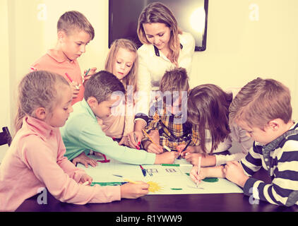 Team of elementary age children and female teacher drawing on one sheet - Stock Photo