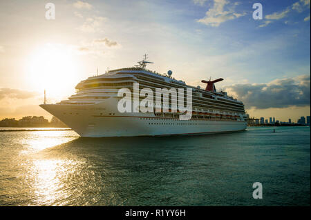 MIAMI - CIRCA AUGUST, 2018: The Carnival Victory Cruise ship passes in front of the city skyline during a sunset departure. - Stock Photo