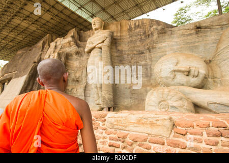 A monk is walking in front of the statue of Reclining Buddha and Monk Ananda at the face of granite rock of Gal Viharaya, Polonnaruwa, Sri Lanka. - Stock Photo