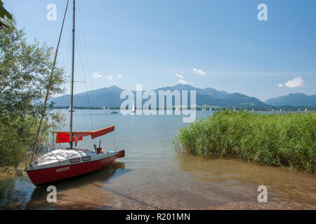 Lake Chiemsee. Sailboat at the shore with island Herreninsel in background, Bavaria, Germany - Stock Photo