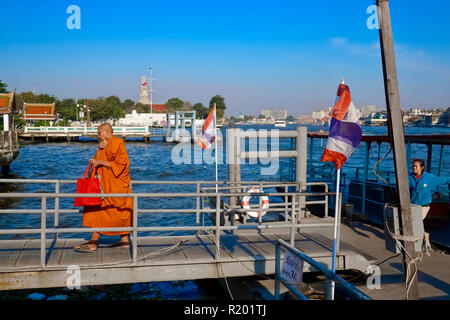 After crossing the Chao Phraya River in Bangkok, Thailand, by ferry, a Buddhist monk leaves the pier, in the b/g Wat Arun, also called Temple of Dawn - Stock Photo