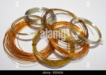 Bundles of jewellery wire for hobby jewellery making. Gold, silver and bronze coloured, colored plated wire isolated on white background - Stock Photo