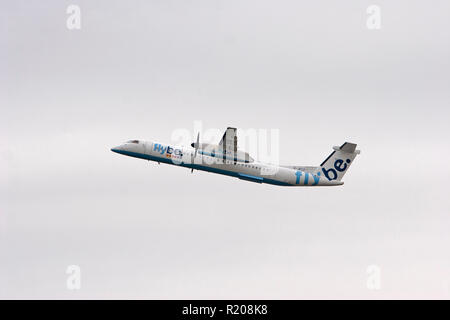 Flybe Dash 8-400 climbing out from Manchester Airport - Stock Photo