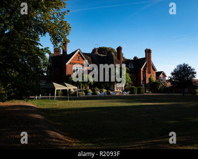 Red Brick Exterior 19th century Victorian Country House. Hotel in early morning sun light Berkshire UK. - Stock Photo