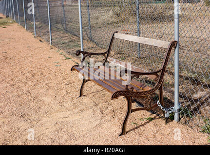 Broken bench secured with a chain and lock in a public park in Alpine, Texas - Stock Photo