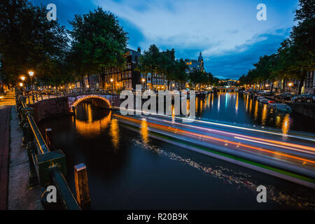 Night in Amsterdam. Lights trails and illuminated bridges on city canal at twilight. Holland, Netherlands. Long exposure - Stock Photo