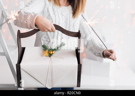 Unrecognizable woman holding Christmas gift in wooden basket and sparklers. Happy winter holidays. Presents for Christmastime celebration. - Stock Photo