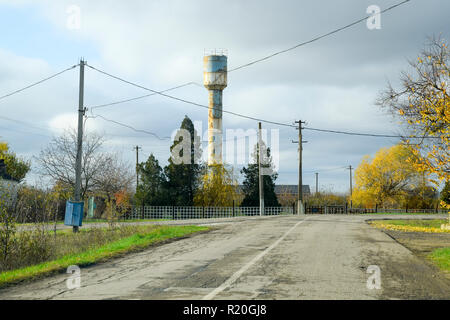 Old water tower in the village. Autumn landscape. - Stock Photo