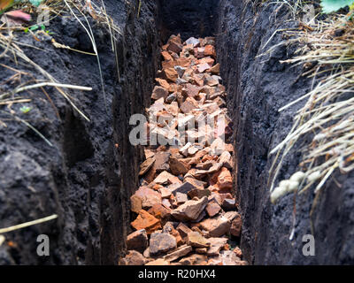 Broken brick piled to the bottom of the trench - Stock Photo