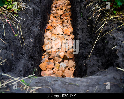 Trench on the garden plot with the remains of broken brick - Stock Photo