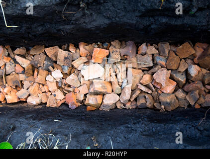Drainage trench filled with broken brick - Stock Photo