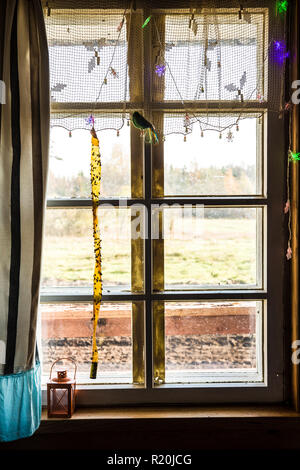 Wide view of country house home window with hanging flypaper with a lot of flies stuck on it. - Stock Photo