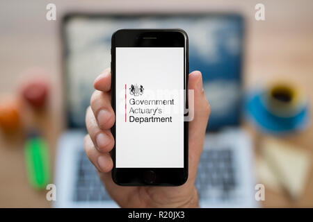A man looks at his iPhone which displays the Government Actuary's Department logo, while sat at his computer desk (Editorial use only). - Stock Photo