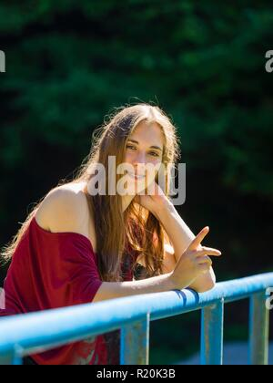 Teeth braces young teen woman eyes-contact looking at camera smiling extending finger to get attention - Stock Photo
