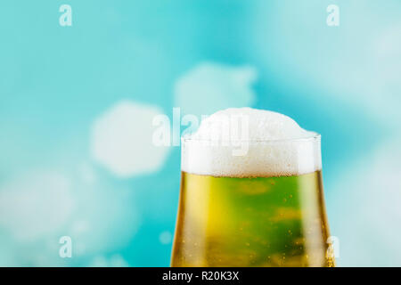 Goblet style beer glass on dark natural wooden table with light blue bokeh background. - Stock Photo