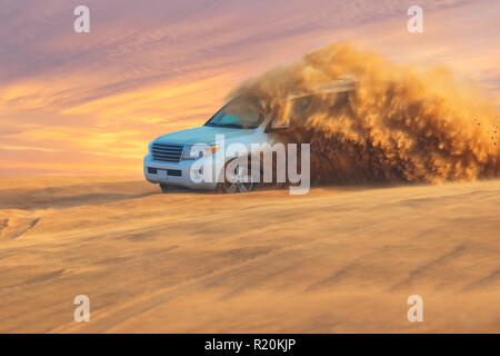 Off-road safari adventure with SUV in Arabian Desert at sunset. Offroad vehicle bashing through sand dunes in Dubai desert. - Stock Photo