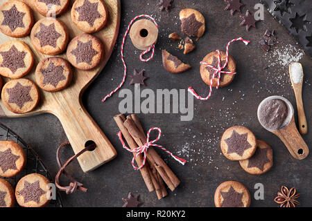Christmas cookies with chocolate star pattern with cinnamon and anise, flat lay on dark brown background - Stock Photo