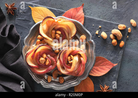 Three homemade puff pastries with rose shaped apple slices on metal plate. Top lay on wooden board with Autumn leaves and caramelized nuts. - Stock Photo