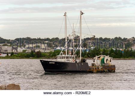 New Bedford, Massachusetts, USA - September 27, 2018: Commercial fishing vessel Justice crossing New Bedford inner harbor - Stock Photo