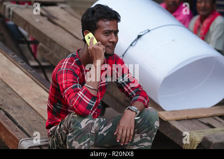 A migrant handcart puller in the Bhendi Bazar area of Mumbai, India, uses a work break to call his family in his native North Indian state of Bihar - Stock Photo