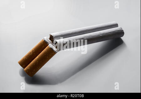 Quit smoking concept, two cigarettes as a double barrel rifle over gray background with copy space - Stock Photo