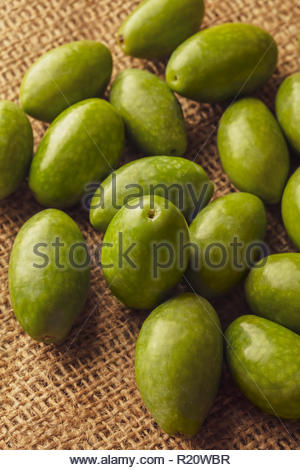 Overhead view with selective focus of freshly harvested Italian green olives on a burlap bag. Olives are an important part of the Mediterranean diet. - Stock Photo