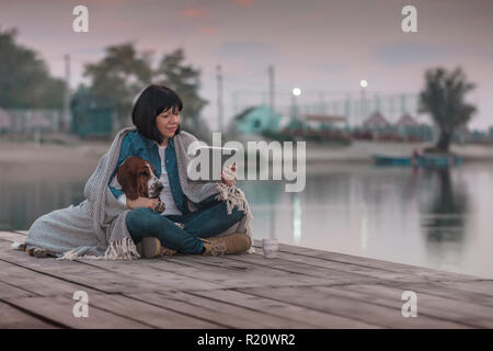 Portrait of beautiful young woman with her dog covered with blanket, using digital tablet while sitting on wooden pier by the river. Sunset - Stock Photo
