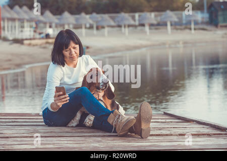 Portrait of beautiful young woman with her dog using mobile phone while sitting on wooden pier by the river. - Stock Photo
